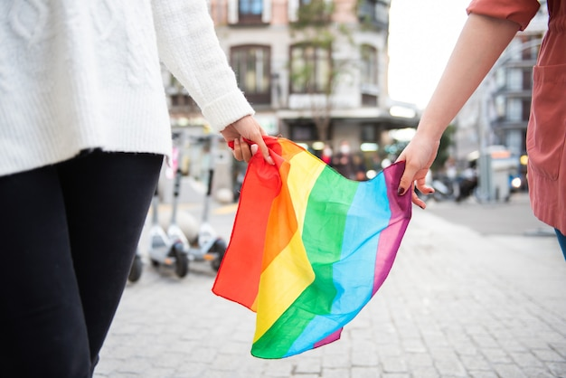 Two girls carrying the rainbow flag around the city