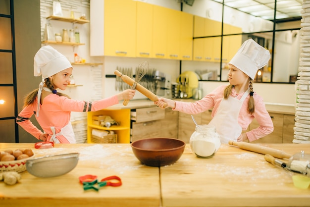 Two girls cooks in caps fights on the kitchen. kids cooking pastry, little chefs holds rolling pin and whisk for whipping