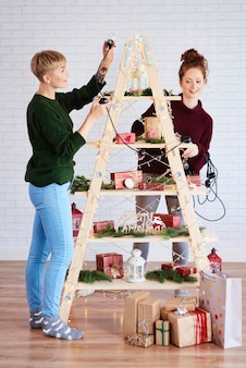 Two girls decorating the christmas tree