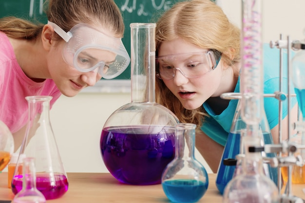 Two girls doing chemical experiments in school