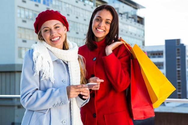 買い物をしているとスマートフォンを保持している2人の女の子 Premium写真