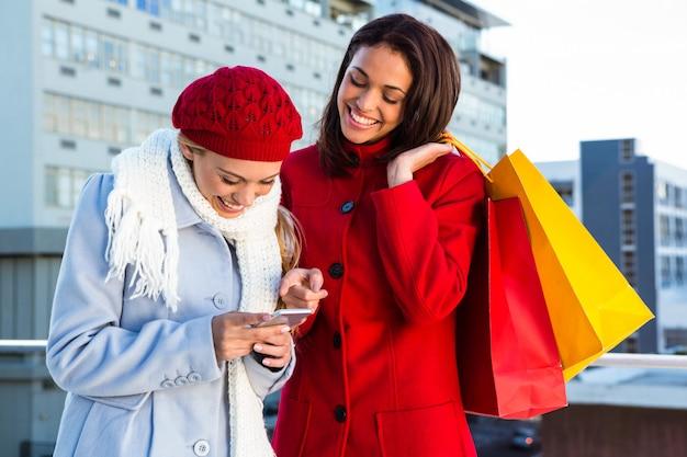 買い物をして、電話を見ている二人の女の子