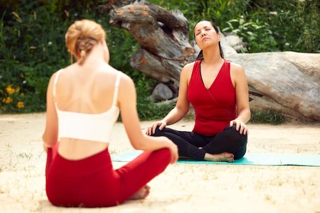 Две девушки занимаются йогой и медитацией на открытом воздухе, парными занятиями йогой, здоровым образом жизни, медитацией и благополучием.