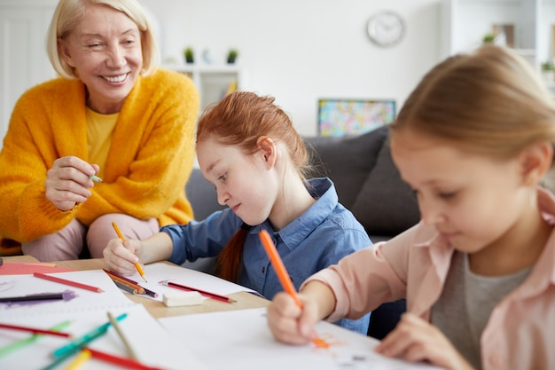 Two girls drawing with mom