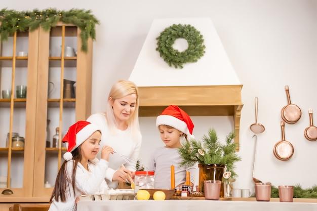 Две девушки в красных шапочках готовят печенье, имбирные пряники к новогоднему празднику, рождеству. вырежьте печенье.