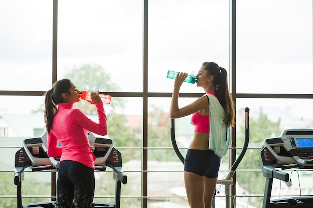 Two girls drinking water in the gym