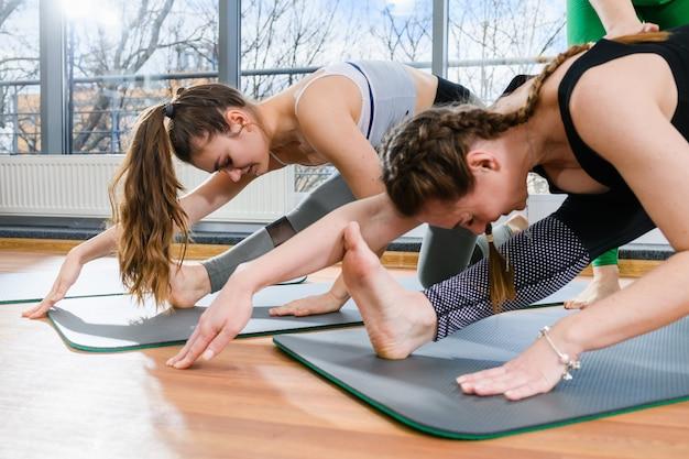 Две девушки во время тяжелых тренировок, растяжки и разминки мышц ног в студии фитнес-йоги