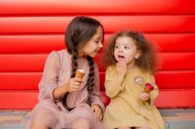 Две девушки едят мороженое у красного забора. одна брюнетка с двумя косичками, вторая - легкий кудрявый локон.