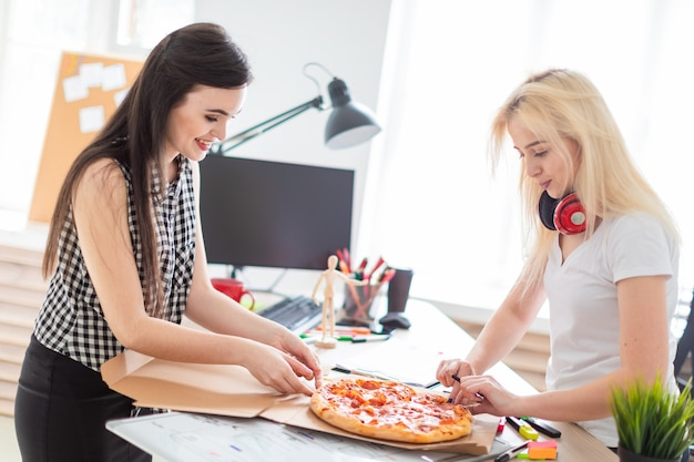 Two girls eating pizza in the office.