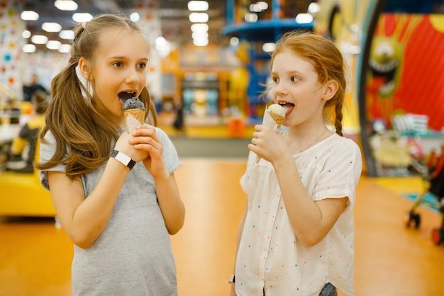 2人の女の子がエンターテインメントセンターでアイスクリームを食べます。休日の子供たちのレジャー、子供の頃の幸せ、遊び場での幸せな子供たち