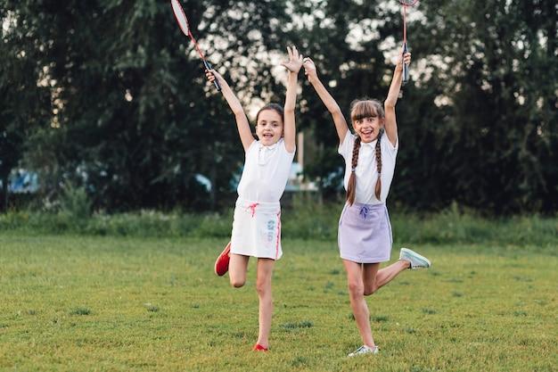 Two girls enjoying in the park holding badminton