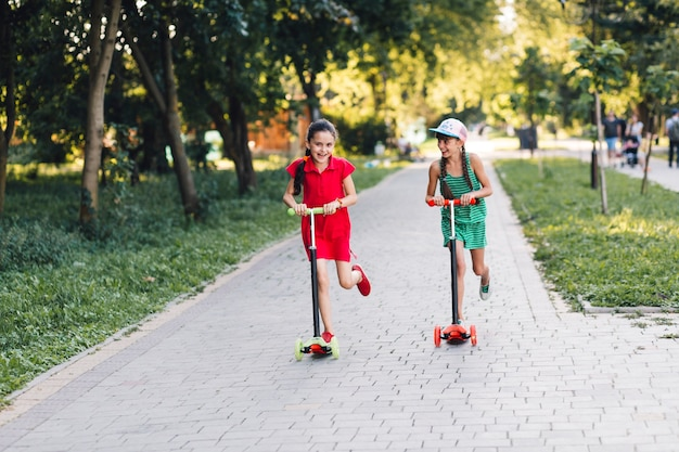 Two girls enjoying riding push scooter in the park