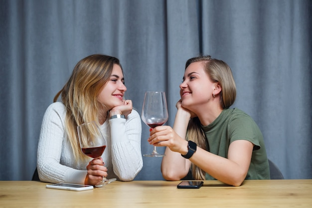 Two girls of european appearance with blond hair are sitting at the table, drinking wine and laughing, relaxing at home, alcohol