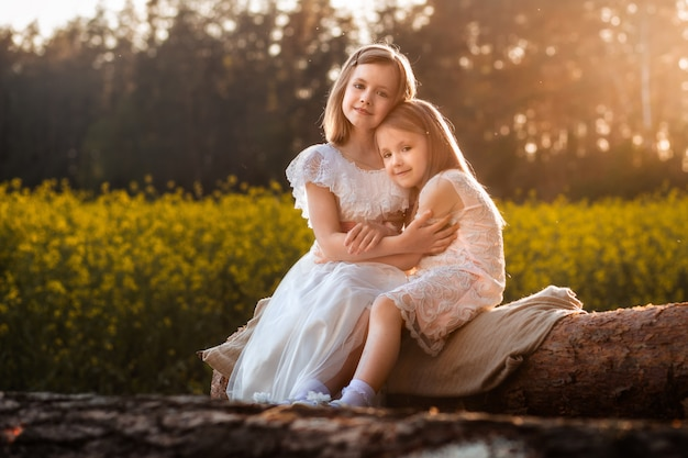 Two girls in a field of rapeseed in summer