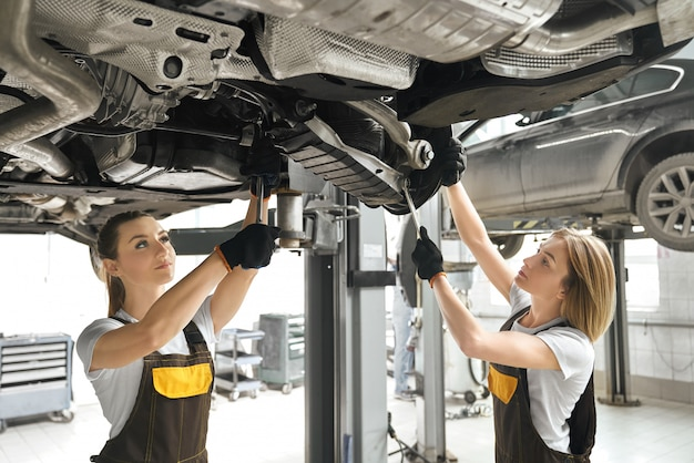 Two girls fixing lifted auto undercarriage, using wrenches.