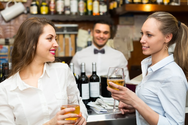Two girls flirting with barman