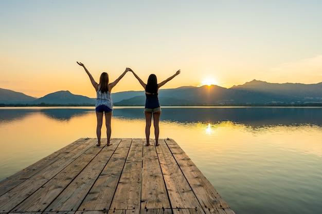 木製の桟橋に立っている夕日を見て精神的な瞑想に焦点を当てた2人の女の子
