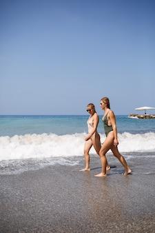 두 여자 친구가 화창한 따뜻한 날 수영복을 입고 바다 모래 사장을 걷고 있다