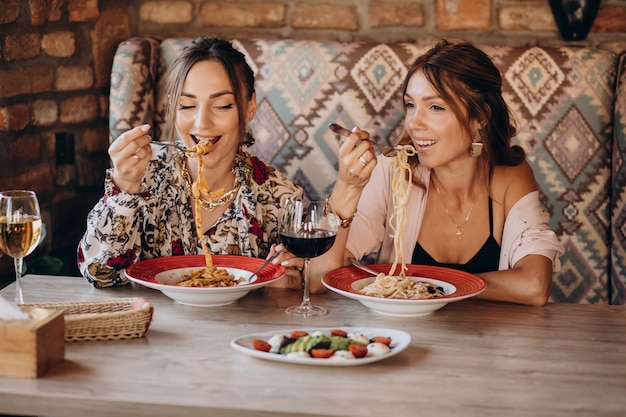 Two girls friends eating pasta in an italian restaurant