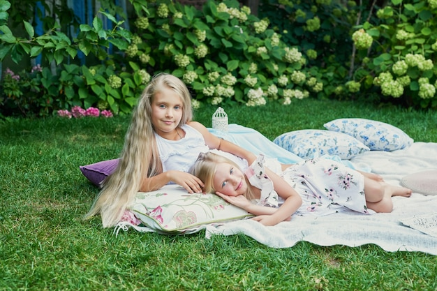 Two girls friends in the garden at a picnic in the summer