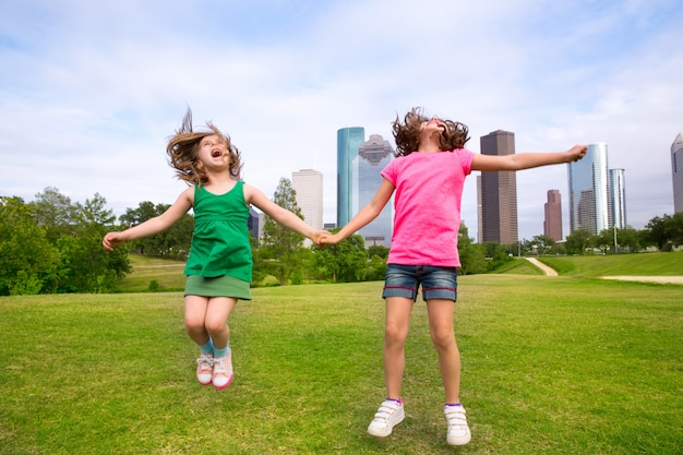 Two girls friends jumping happy holding hand in city skyline