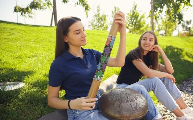 여름 도시 거리에서 음악을 연주하는 두 여자 친구