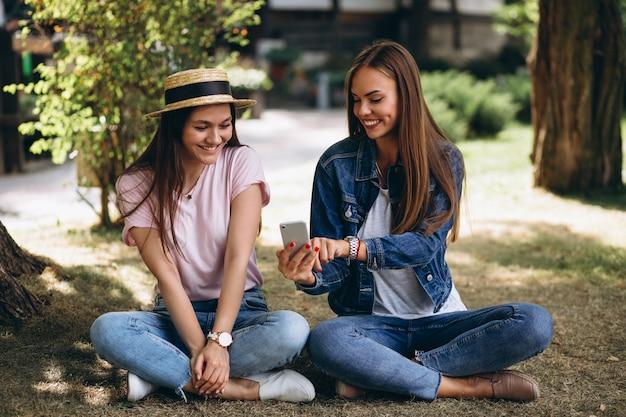 Две девушки друзья, сидящие в парке