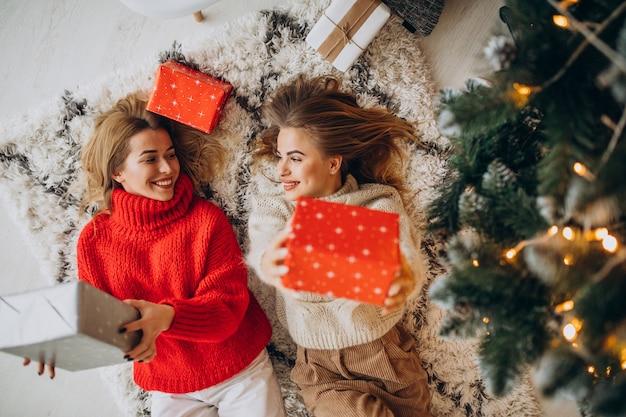 나무 옆에 크리스마스 선물에 앉아 두 여자 친구