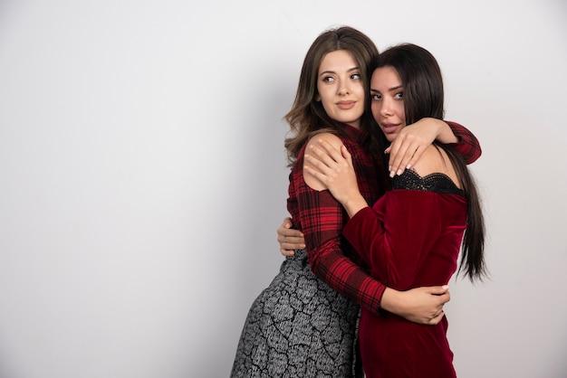 Две подруги стояли и обнимали друг друга.