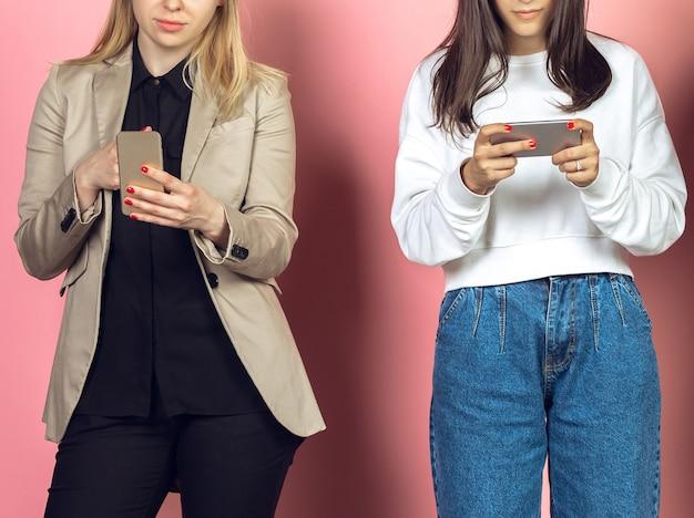 2人の女の子、モバイルスマートフォンを使用している友人。新しいテクノロジーのトレンドに対するティーンエイジャーの中毒。閉じる。