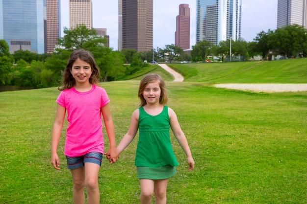 Two girls friends walking holding hand in urban skyline