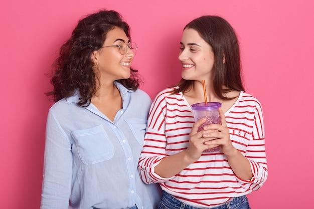 Две девушки развлекаются с безалкогольным напитком