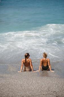 Две девушки-подруги сидят на морском песчаном берегу и волны мочили их в купальниках в солнечный теплый день