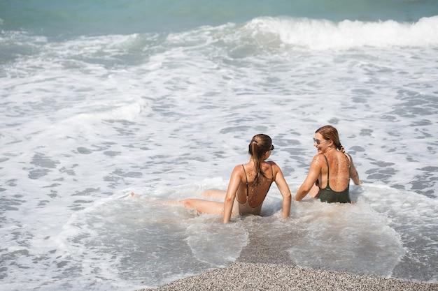 두 여자 여자 친구가 바다 모래 사장에 앉아 있고 화창한 따뜻한 날에 파도가 수영복에 그들을 적셨다
