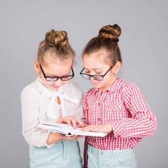 Two girls in glasses reading book