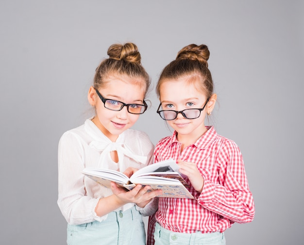 Two girls in glasses standing with book