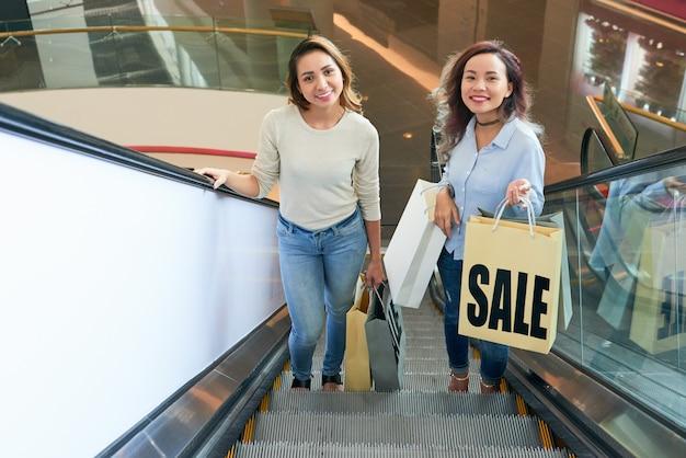 Две девушки поднимаются по лестнице на эскалаторе в торговом центре