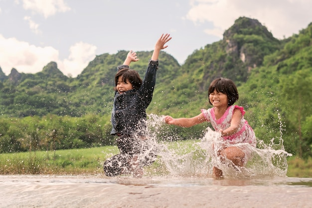 Two girls happy playing in the river. children having fun outdoors on summer lifestyle