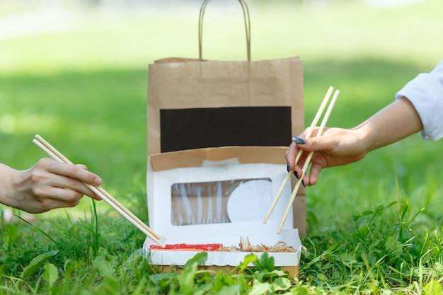 Две девушки ужинают японскими суши-роллами на летнем пикнике