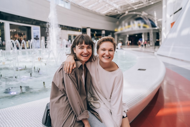 Две девушки развлекаются в торговом центре
