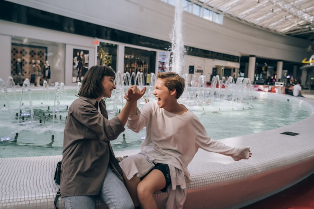 Two girls have fun in the mall, a fountain