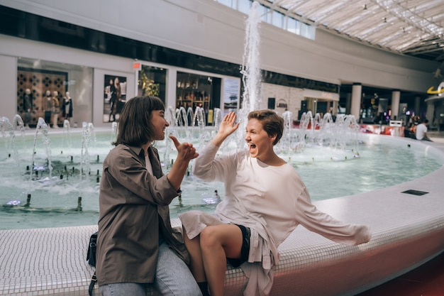 Two girls have fun in the mall, next to a fountain