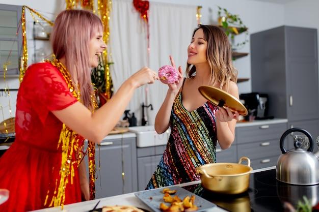 Две девушки веселятся на кухне после вечеринки