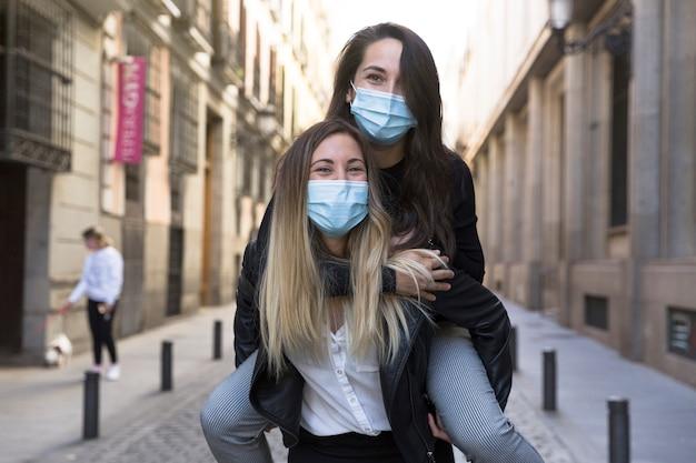 通りで楽しんでいる2人の女の子。彼らは医療用マスクを着用しています。