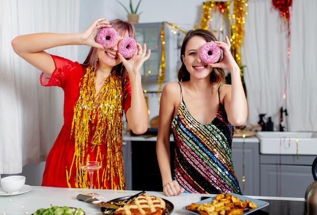 パーティーの後、キッチンでドーナツを楽しんでいる2人の女の子