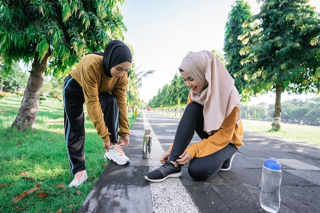 Two girls in headscarves carrying drinking bottles squatting on the floor chatting while holding and fixing shoelaces after exercising together in the afternoon