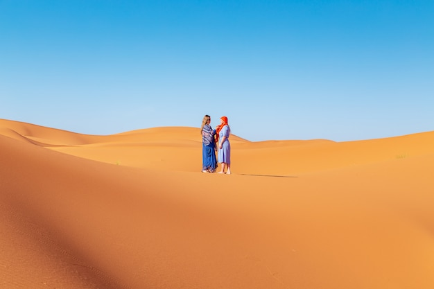 Two girls in headscarves in the sahara desert.