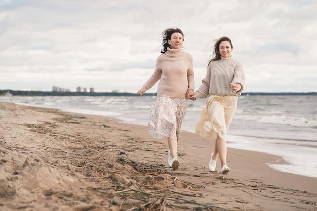 손을 잡고 해변을 달리는 두 소녀 자매는 사랑에 빠진 부부와 함께 즐거운 시간을...
