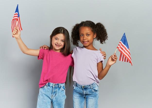 アメリカの国旗を持っている2人の女の子