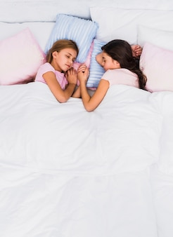 Two girls holding each other's hand sleeping together on bed